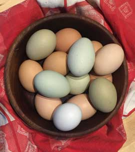 A wooden bowl full of colored eggs